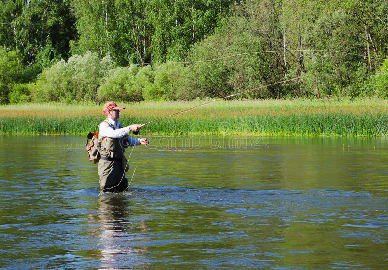 Fisherman catches of chub fly fishing in the Chusovaya river stock image