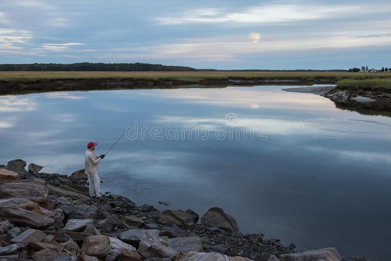 Fisherman catches fish on the evening lake. stock photo