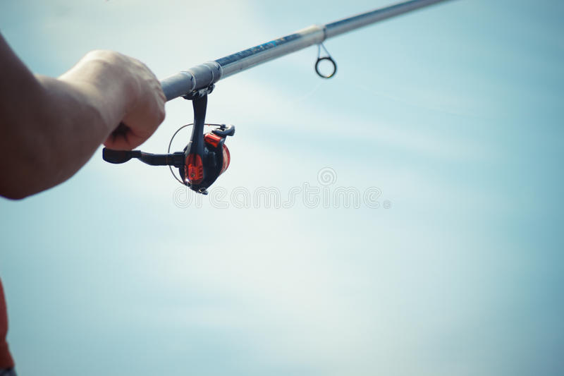 Fisherman catches a fish. Hands of a fisherman with a spinning rod in hand closeup. Spin fishing reel.  royalty free stock photo