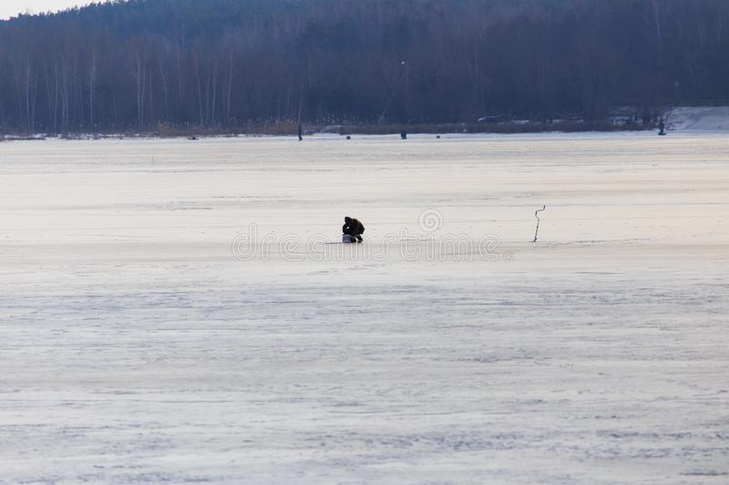 Fisherman catches fish on ice in winter royalty free stock photos