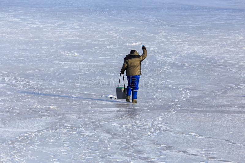 Fisherman catches fish on ice in winter stock photos