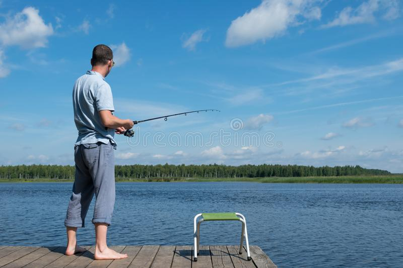 Fisherman catches fish on the river against the backdrop of a beautiful blue sky stock images