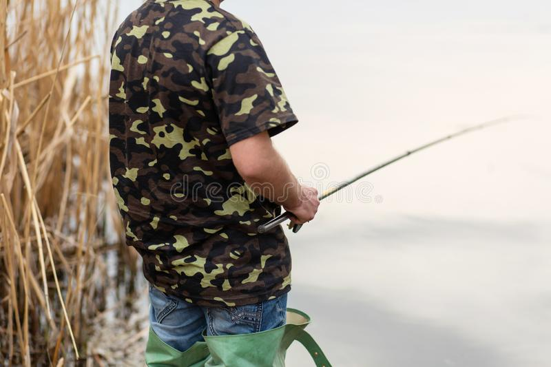Fisherman catches fish by the river. Man holds fishing pole royalty free stock images