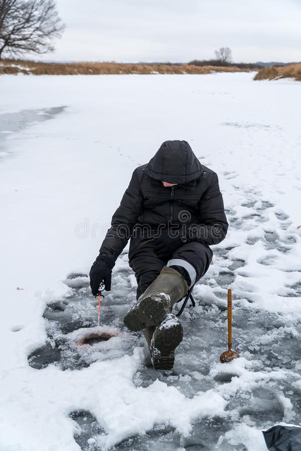 Fisherman catches a fish on winter fishing stock photography