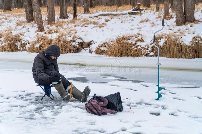 Fisherman catches a fish on winter fishing royalty free stock photography