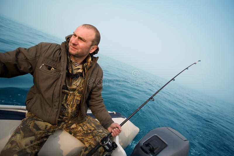 Fisherman catches salmon trolling royalty free stock photos