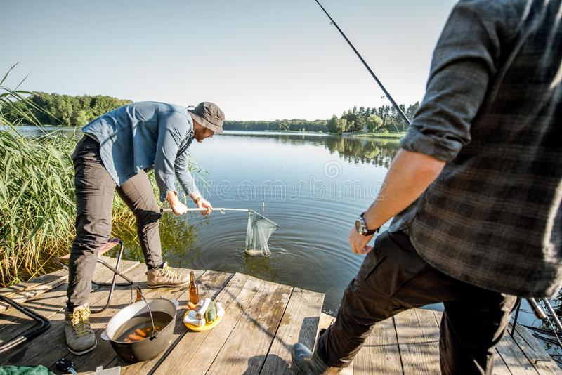 Fisherman catching fish. Fisherman catching big fish with fishing net on the lake in the morning stock images