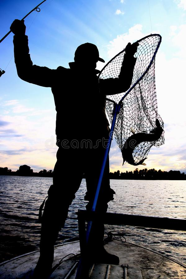 Fisherman with a catching fish on river. Boat stock photography