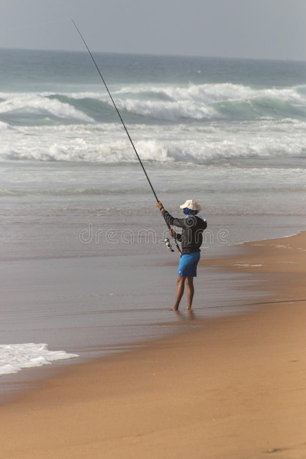 A Fisherman. A close up view of the side of a fisherman fishing on the shore on a beautiful sunny summers day on a durban beach royalty free stock images