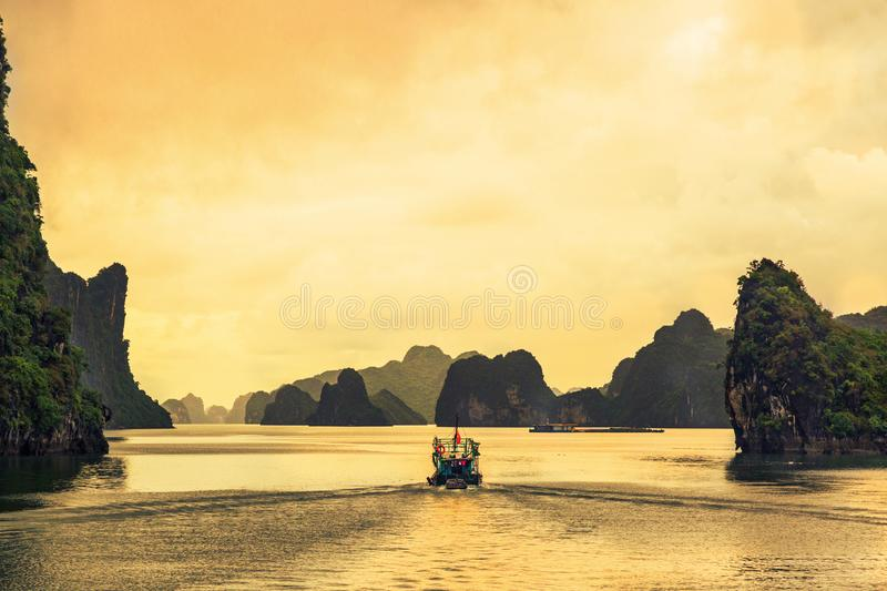 Fisherman coming home in sunset at Halong bay, the most beautiful bay on the world. Ha Long Bay. UNESCO World Heritage site. Ha Long Bay, in the Gulf of Tonkin royalty free stock photography