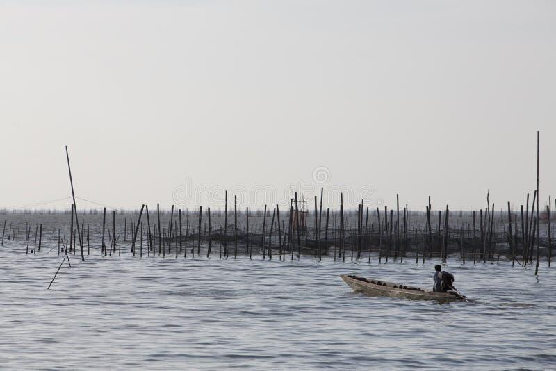 Fisherman crossing a lake stock photography