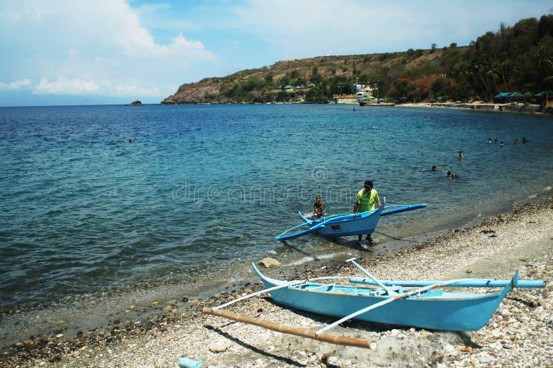 Fisherman dragging his small boat to be parked at sea shore. royalty free stock photos