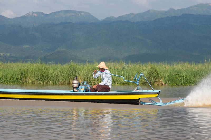 Fisherman driving in wooden boat on inle lake in myanmar asia royalty free stock images