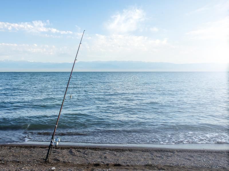 .Fisherman fishes early in the morning on the shore. Fishing rod and spinning. Camping. royalty free stock photos