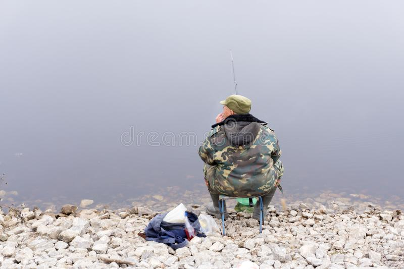 Fisherman fishes in the river. Middle aged man. royalty free stock images