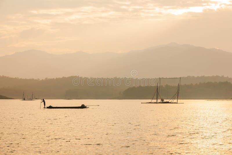 Fisherman on fishing boat in The Sirikit Dam, raft dip net and sunset sky backgrounds. Golden sun setting shines down around the. Lake. Beautiful glistening stock image