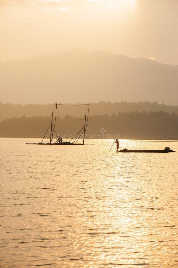 Fisherman on fishing boat in The Sirikit Dam, raft dip net and sunset sky backgrounds. Golden sun setting shines down around the. Lake. Beautiful glistening stock photography