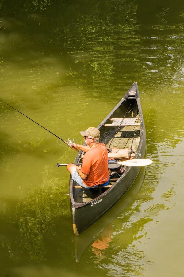Fisherman Fishing From a Canoe. Roanoke County, VA – June 30th: Fisherman in a canoe fishing for smallmouth bass on the Roanoke River next to the Roanoke royalty free stock photo