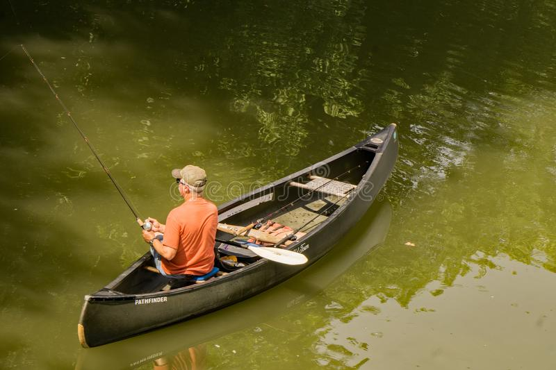 Fisherman Fishing From a Canoe - 2. Roanoke County, VA – June 30th: Fisherman in a canoe fishing for smallmouth bass on the Roanoke River next to the Roanoke royalty free stock photos