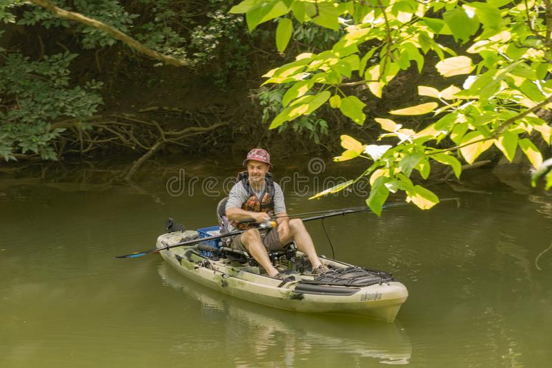 Fisherman Fishing Casting from a Kayak. Roanoke County, VA – June 30th: A fisherman fishing from kayaks for smallmouth bass on the Roanoke River next to royalty free stock image