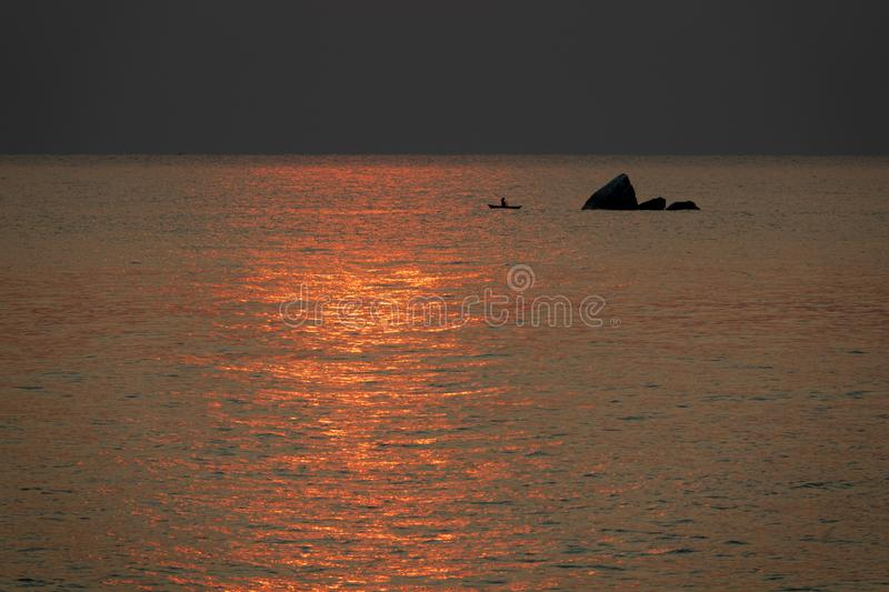 Fisherman fishing near rock at sunrise in Malawi lake, high contrast royalty free stock image