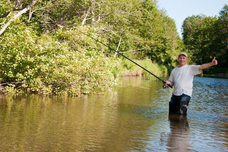 Fisherman fishing on a river. A fisherman fishing on a river stock photo