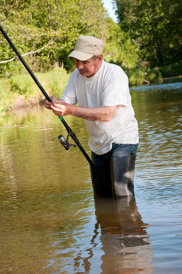 A fisherman fishing on a river. Senior fisherman fishing on a river stock photos