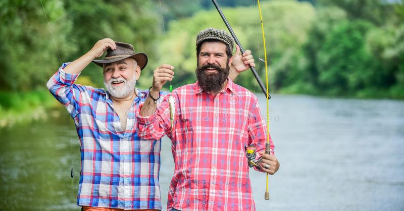Fisherman with fishing rod. Bearded men catching fish. Mature man with friend fishing. Summer vacation. Happy cheerful stock photo