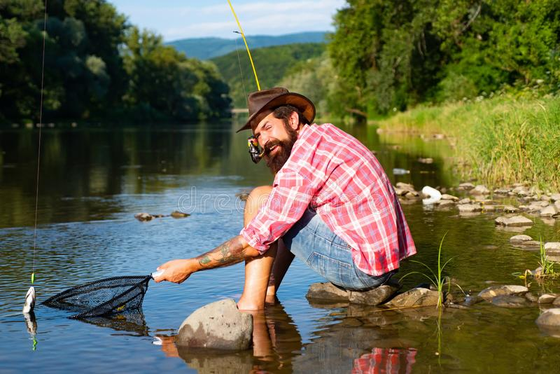 A fisherman with fishing rod on the river. Brown trout fish. Summer holidays and people concept. Trout. Trout on a hook royalty free stock photo