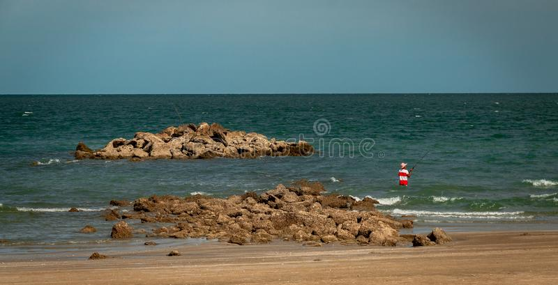 Fisherman with fishing rod in the sea in Thailand alone. royalty free stock photos