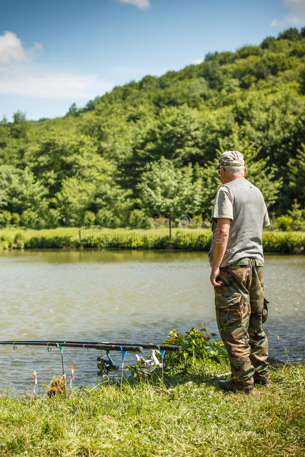 Fisherman. With fishing rod standing on lakeside royalty free stock photography