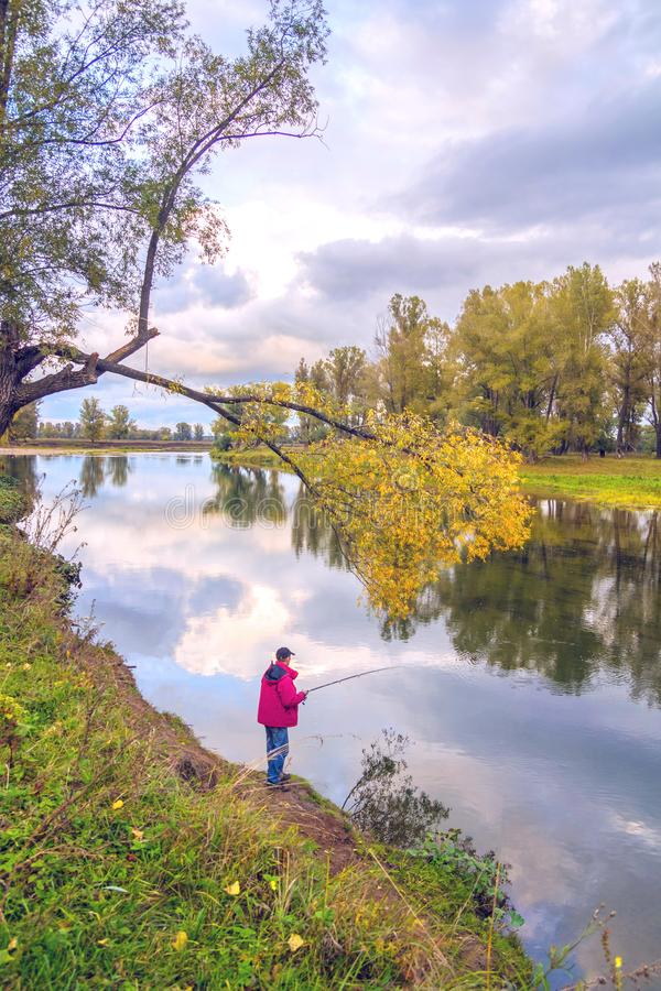 Fisherman with a fishing rod stands on the banks of the river in the autumn forest royalty free stock image