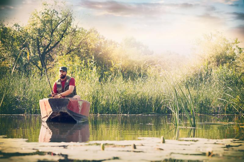 Fisherman with fishing rods is fishing in a wooden boat against background of beautiful nature and lake or river. stock image