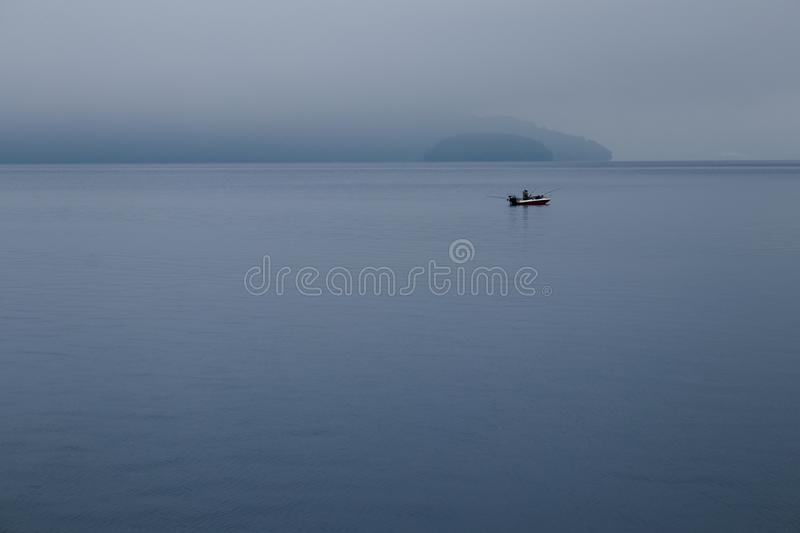 Fisherman fishing in speed boat, The boat floating in Toya Lake surrounded with fog in cloudy day at Japan. royalty free stock image