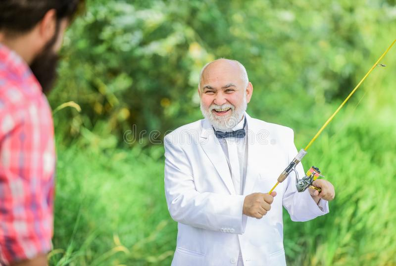 Fisherman in formal suit. Successful catch. Senior man fishing. Elegant bearded man fishing. Luxury life concept. Grandpa is my name, fishing is my game. Hobby stock photo