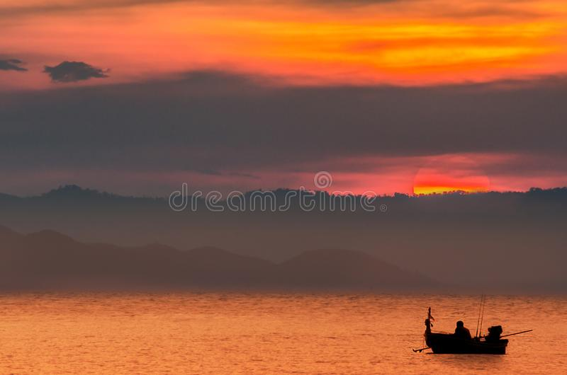 A fisherman has alone on the sea in the evening with big sunset. A fisherman has alone on the sea in the evening with sunset time at Thailand royalty free stock photo