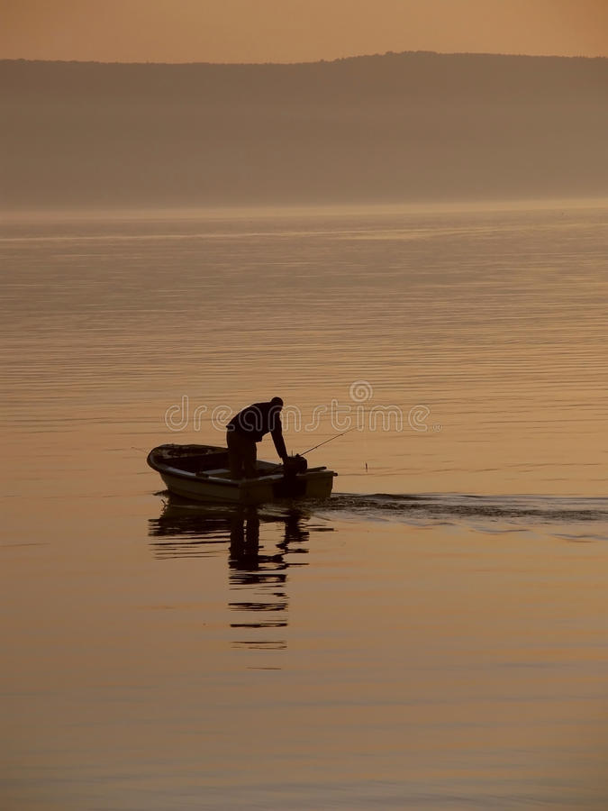 Fisherman in the haze at sea royalty free stock photography