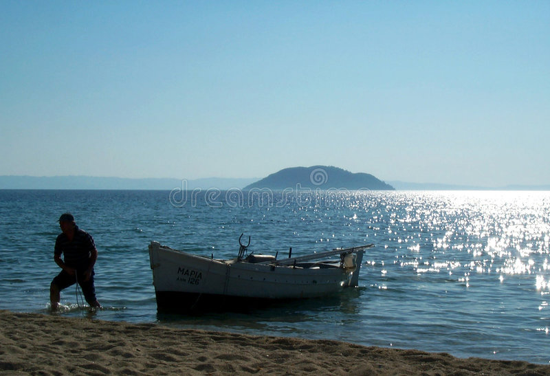 Fisherman and his boat. A Greek fisherman pulls his boat ashore in Northern Greece royalty free stock photography