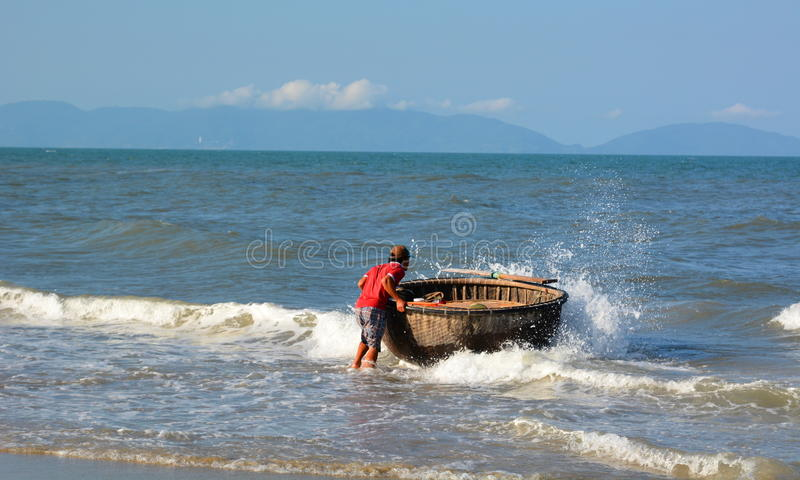 Fisherman and his traditional round boat (tung chai). An Bang beach. Hoi An. Vietnam royalty free stock images