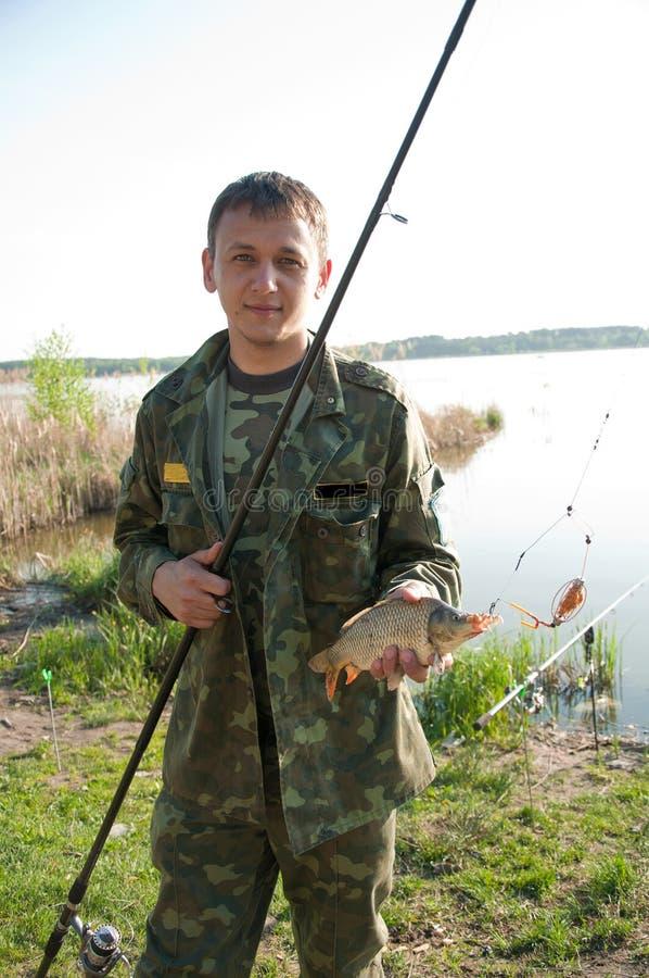 Download Fisherman Holding Carp On The Shoreline Stock Image - Image of outdoors, fisherman: 25600549