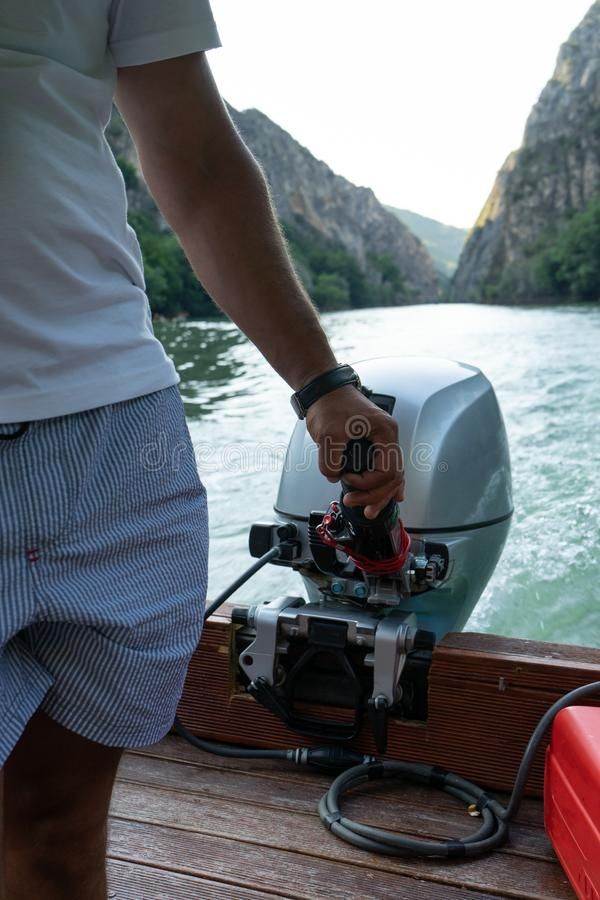 Fisherman holding small motor to drive the boat. A pilot control the power of the speed while navigate inside a valley. Arm of a. Man with the engine of the royalty free stock photo