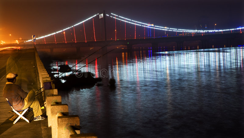 Fisherman at Hun River. A fisherman on the shore of the Hun River in Fuxin City, China, with bridge with red lights on the background stock image