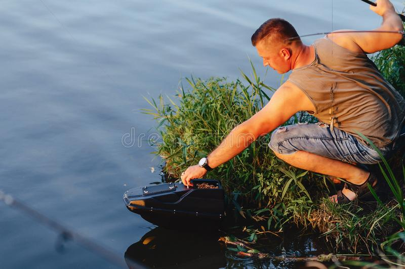 Fisherman imports bait by boat on lake for fishing royalty free stock photography