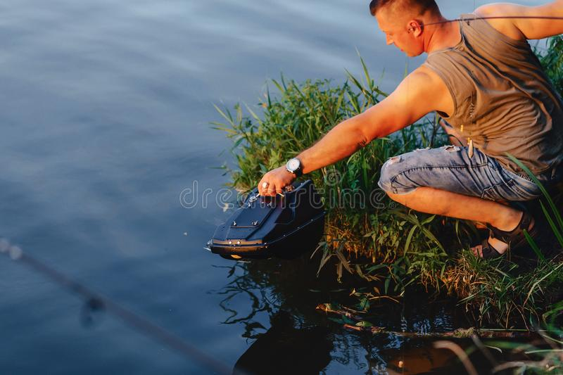 Fisherman imports bait by boat on lake for fishing stock image