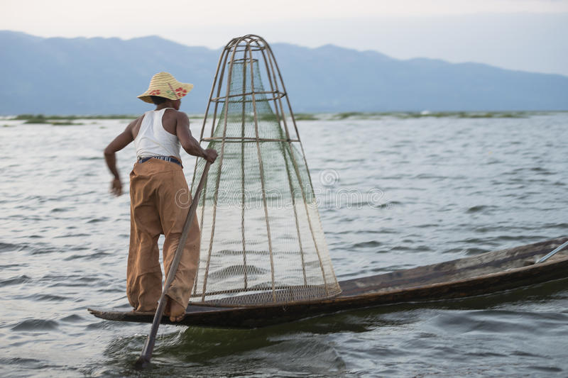 Fisherman on the Inle lake in Myanmar. A leg rowing fisherman on Inle Lake in Shan State in Myanmar (Burma).This unique style of rowing evolved because the royalty free stock photography