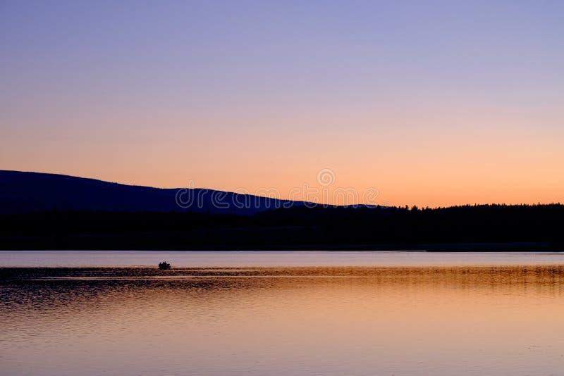 Fisherman on Lake at sunset royalty free stock photography