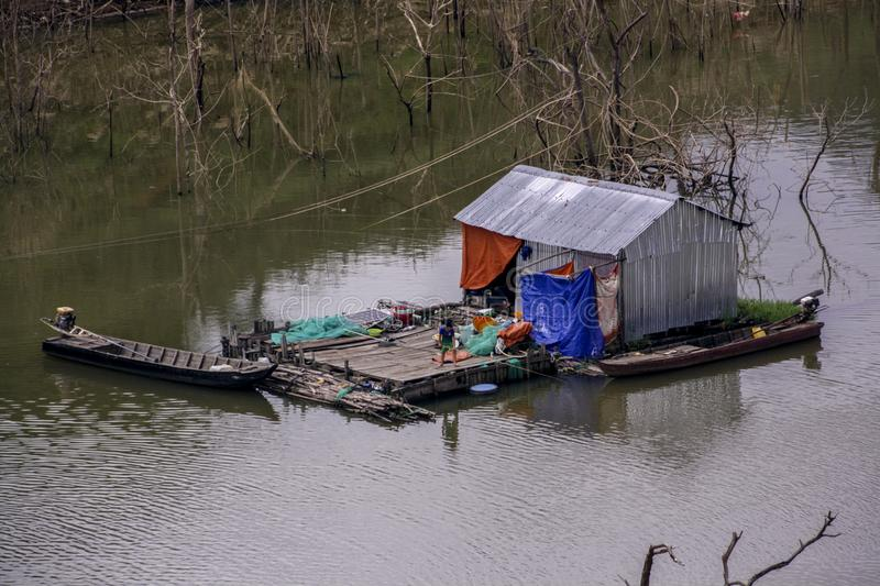 The fisherman lives in the middle of the river in a shack house made of tin sheets royalty free stock photo