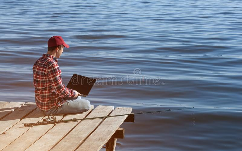 Fisherman man works on a laptop, sits on a wooden pier near the lake, next to it there is a fishing pole. A fisherman man works on a laptop, sits on a wooden stock images