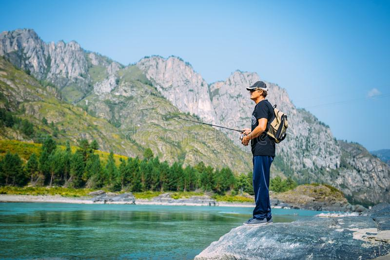 Fisherman on the mountain river at the nice summer day. Trout fly fishing in the mountain river with mountains in background stock photography