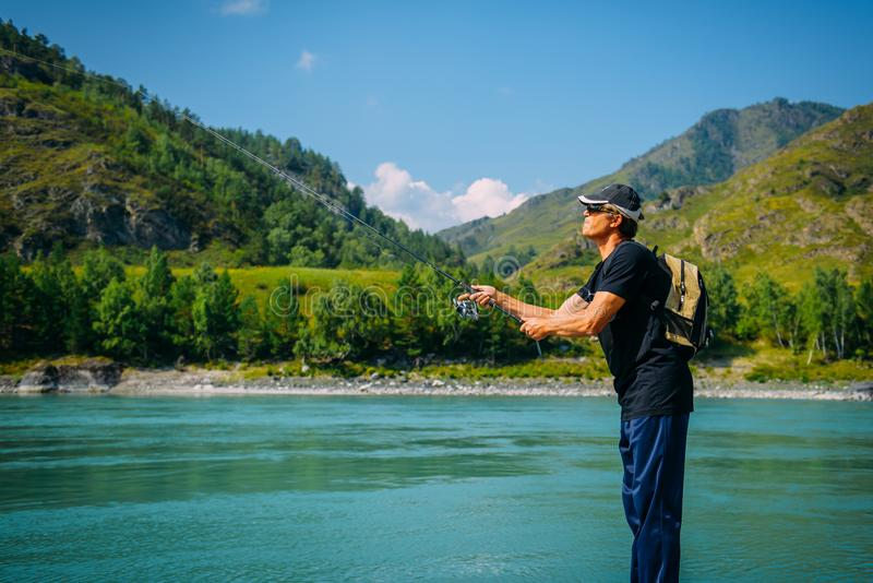 Fisherman on the mountain river at the nice summer day. Trout fly fishing in the mountain river with mountains in background. Spinning stock photos